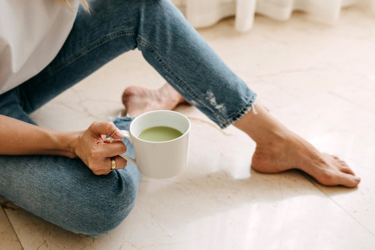 Close-up of a woman sitting on the floor, drinking matcha tea from a white cup.