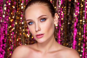 Beauty portrait of a High Fashion model woman in colorful bright neon lights posing in studio, night club On colourful vivid sequin background.