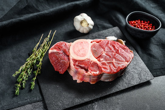 Raw beef ossobuco on a table with spices. Black background. Top view