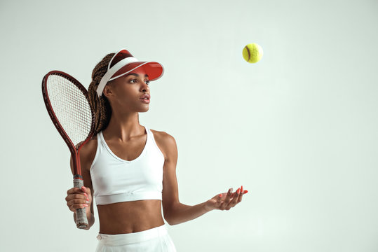 Ready to play. Portrait of young african woman in sports clothes holding tennis racket on her shoulder and throwing tennis ball while standing against grey background