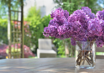 beautiful bouquet of purple lilac flowers on a wooden table in garden