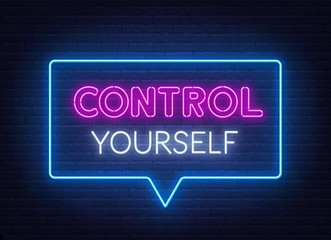 Control Yourself neon lettering on brick wall background.
