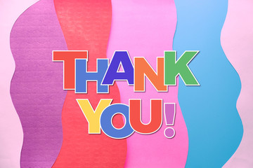 Thank you text in rainbow letters on layered colorful abstract paper background. Thank you doctors, nurses, medical teams and key workers taking care of our life during Covid-19 pandemics!