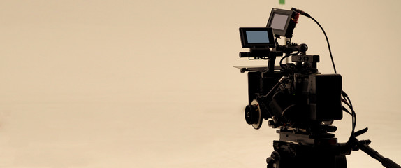 Behind the shooting production crew team and hd video camera and equipment in studio which includes big tripod, soft box light, monitors, lens for making online web film or movie or live broadcasting.