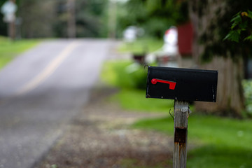 a traditional American mailbox on the side of a village road