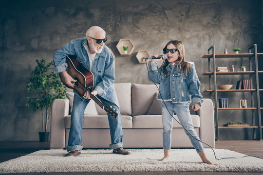 Photo of two people excited grandpa play guitar small granddaughter mic singing cool style trendy sun specs denim clothes repetition school concert stay home quarantine living room indoors