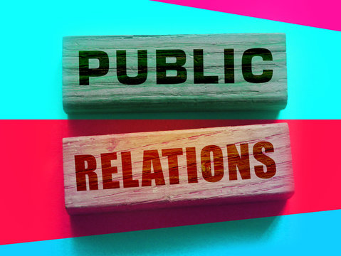 Public relation written in wooden blocks on a fluorescent red and cyan background. PR business concept