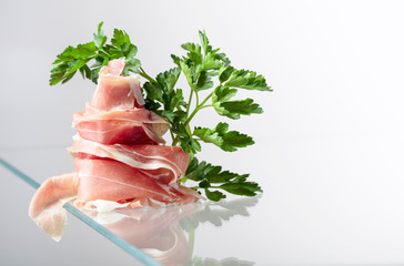 Wall Mural - Prosciutto with parsley on a glass table.
