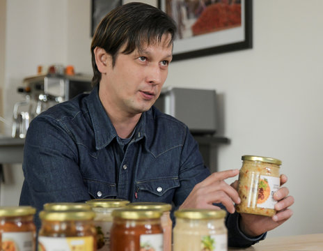 """Alexander Khasanov, founder of the company """"Restaurant from a Jar"""" producing and delivering restaurant-quality ready meals squeezed into glass jars, shows the company's products in Moscow"""