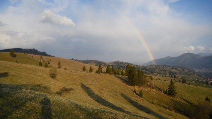 Rainbow over stormy sky. Rural landscape with rainbow over dark stormy sky in a countryside at spring day.
