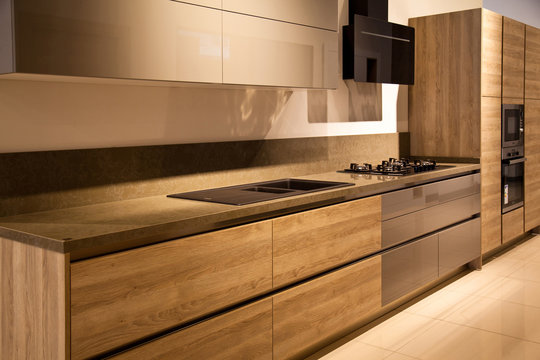 Interior of modern kitchen equipment, grey and oak cabinets