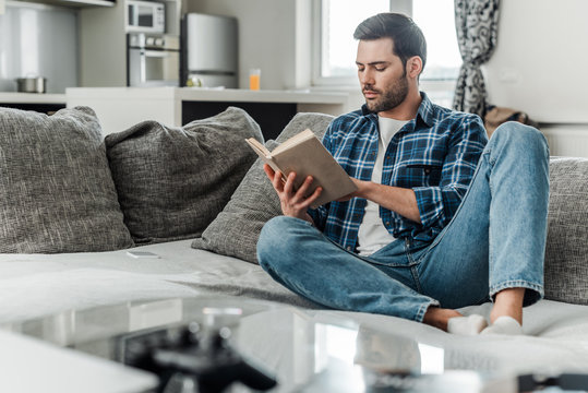 Selective focus of handsome man reading book on couch at home