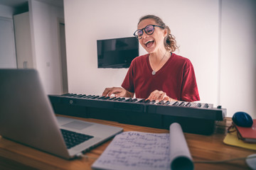 Young girl woman learns to sing and play the piano from a video conference from a laptop in internet. Education video calls self education Wall mural