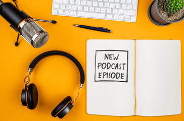 top view of text NEW PODCAST EPISODE on notepad on desk with microphone, computer keyboard and headphones, podcasting concept