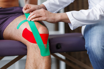 Kinesiology taping.Physical therapist applying kinesiology tape to patient knee.Therapist treating injured knee of young athlete.Post traumatic rehabilitation, sport physical therapy,recovery concept.