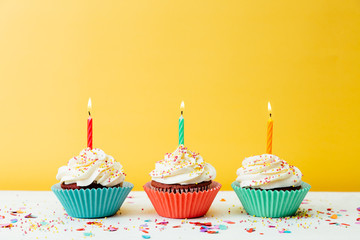 Cupcakes for birthday party on yellow background