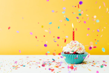 Birthday cupcake wih confetti on yellow background