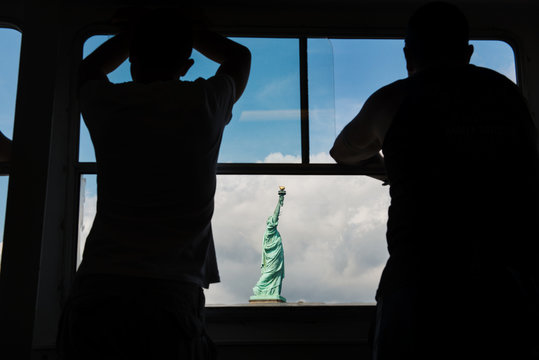 silhouette of two people admiring the statue of liberty from the ferry, New York