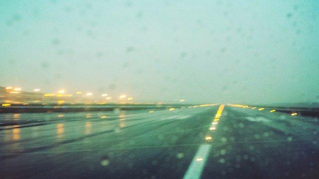 Airport Runway Seen Through Wet Glass Window At Dusk
