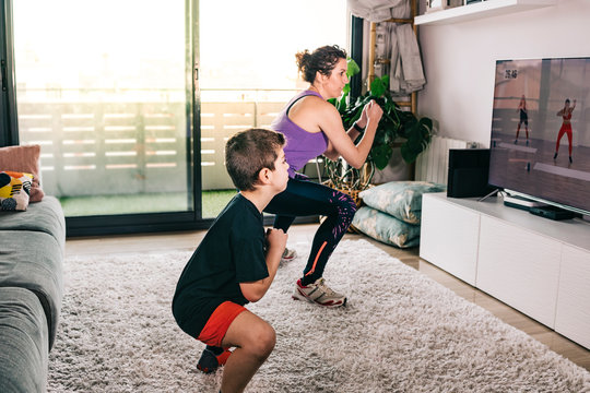 Mother and son exercising with a virtual class on tv