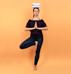Charming and elegant woman in the tree yoga pose meditates while balancing some books on her head