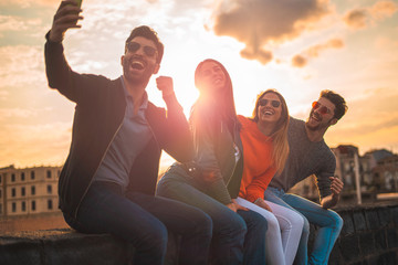 Group of happy young influencers people taking a selfie sitting on a bench outdoors in the sunset. Real backlight flare. Leisure activities lifestyle concept.