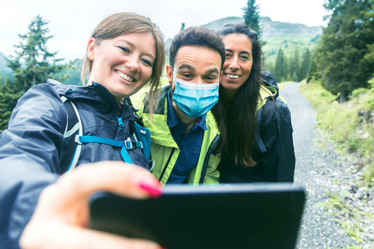 Hiking friends in protective masks standing on mountain terrain taking a selfie on a foggy day