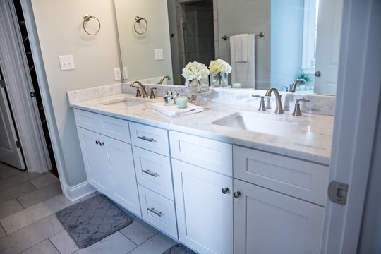All white and gray modern contemporary master bathroom in a small new construction house with tiled floor, a vanity cabinet, double sinks and a mirror