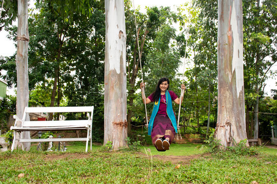 Thai woman sit relax and playing on wooden bench swings toy in garden of resort at riverside Mae Khlong or Meklong river in Ban Pong at Ratchaburi Province, Thailand