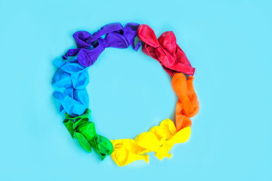 LGBT flag painted isolated on a blue background. Multi-colored LGBT symbol of colored balls. Copy space, banner