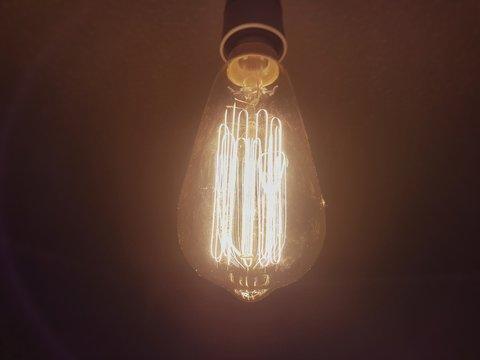 Close-up Of Illuminated Light Bulb Hanging Against Black Background