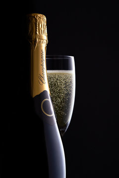 Champagne bottle and full glass with clear bubbles moody black background, high-end concept for luxury clamorous celebration, curves, silhouette, bottle shape close up.