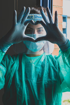 A woman wearing a medical mask, face shield and hands with a latex glove shows the symbol of the heart. Doctor for the heart. We love our medical professionals.