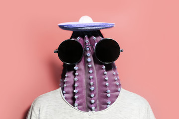 Minimal pop-art collage portrait of green cactus-headed man wearing black round shades and mexican hat on background of coral pink color.
