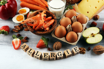 Allergy food concept. Allergy food as almonds, milk, cheese, strawberry, eggs, peanuts and .crustaceans or shrimps with wooden letter in german allergie