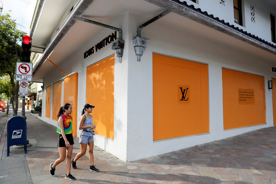 Two women walk past a boarded up luxury shop in the tourist district of Waikiki as many businesses have temporarily closed across Hawaii due to the business downturn caused by the coronavirus disease (COVID-19) in Honolulu