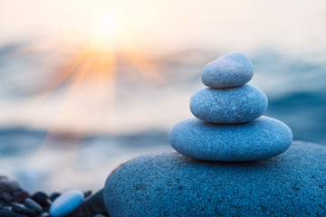 Photo sur cadre textile Zen pierres a sable rock pebble pyramid, zen stones on sea beach, morning sunrise, meditation, spa, harmony, calm background, balance concept, copy space