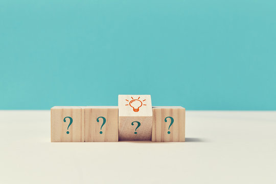 Questions and answers. Creative idea. Think different. Innovation. Wooden cubes with question marks, lightbulb sign
