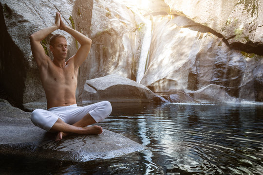 young athletic boy doing iodine and meditation in a waterfall