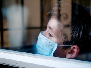 Boy with a medical mask looks sadly out of the window during his confinement because of convid 19