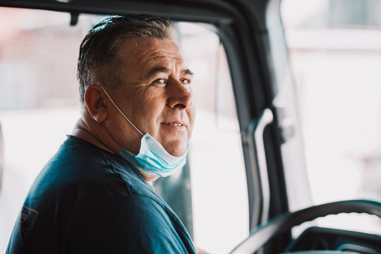 Truck driver inside the cabin with a medical mask on his face