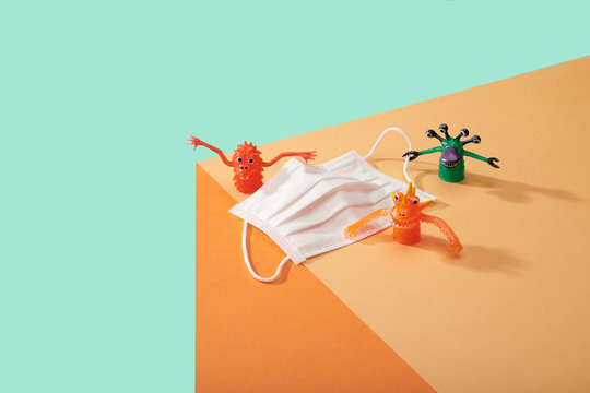 Corona Virus Covid 19 White particle face mask with germs cooties toys lined up on edge of table surface kid friendly image