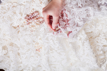 Cropped Hand Of Woman Stitching Pearls On White Wedding Dress