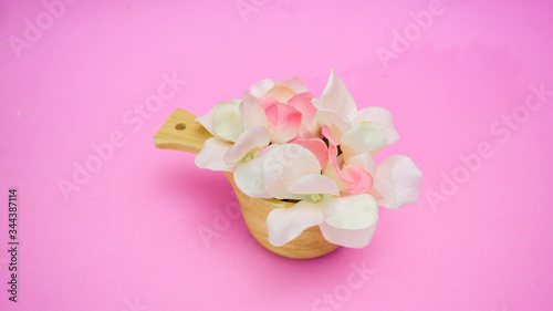 Wall mural Flowers in a wooden cup on pink background