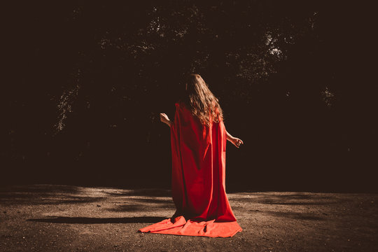 Rear View Of Woman Wearing Red Cape While Standing On Footpath At Night