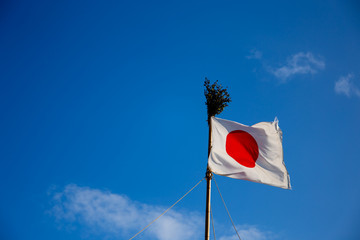 Low Angle View Of Japanese Flag Against Blue Sky