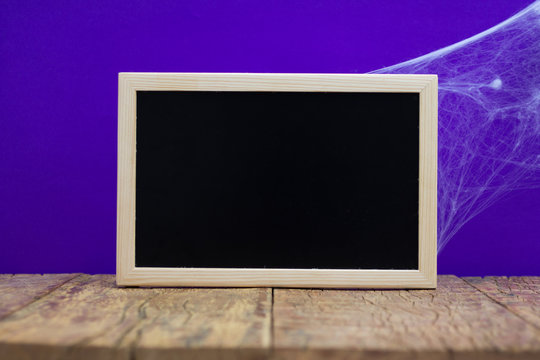 Close-up Of Blank Blackboard On Table Against Blue Background