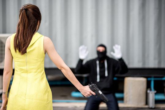 Woman With Gun Standing In Front Of Burglar Kneeling On Footpath