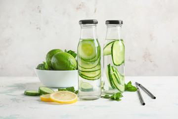 Fotobehang - Bottles of cucumber infused water on table