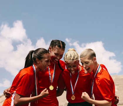 Woman football team with medals celebrating victory